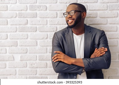 Handsome Afro American businessman in gray classic jacket and glasses is smiling, standing with crossed arms against brick wall
