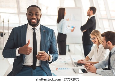 Handsome Afro American businessman in suit is looking at camera and smiling, business conference in the background