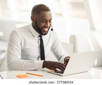 Handsome Afro American businessman in suit and headset is smiling while working with laptop in office