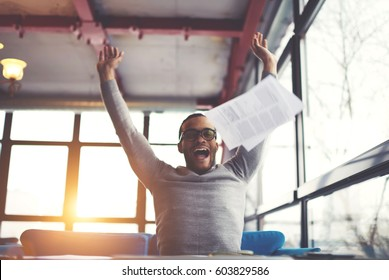 Handsome afro american male international student feeling happiness completed coursework creation getting good mark on university quality control ready for summer vacation sitting in cafeteria