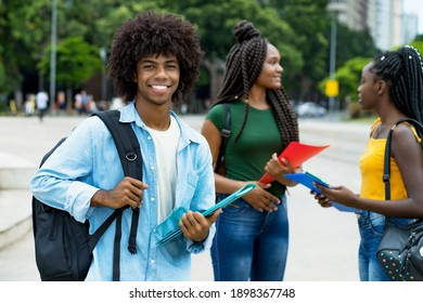 Handsome afro american male student with group of young adults outdoor in city in summer