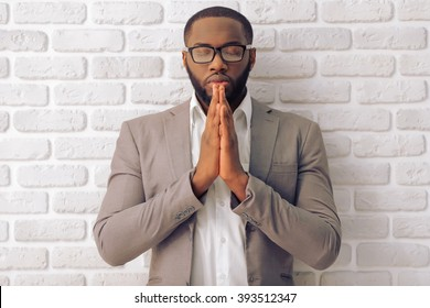 Handsome Afro American man in classic suit and glasses is keeping palms together like praying, standing against white brick wall