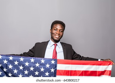Handsome Afro American man in classic suit is smiling standing with American flag