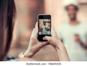 Handsome Afro American man is holding a cup and posing at camera while walking in city, girl takes a photo, phone in focus