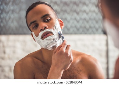 Handsome Afro American man is shaving using a razor while looking into the mirror in bathroom
