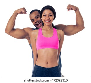 Handsome Afro American man is showing muscles while standing behind beautiful Afro American girl. Both are in sports clothes looking at camera and smiling, isolated on white background