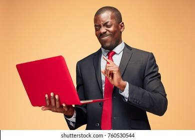 Handsome Afro American man sitting and using a laptop