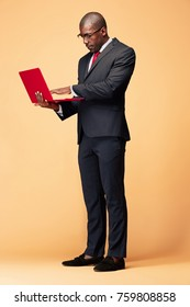 Handsome Afro American man standing with a laptop