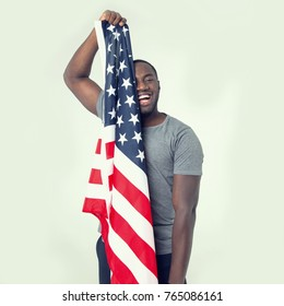 Handsome afro american man with united states flag in hands. Smiling face. Successful confident man. Patriotic male.