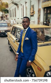 Handsome afro-american fashion model in a blue suit and yellow waistcoat posing near car.