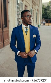 Handsome afro-american fashion model in a blue suit and yellow waistcoat posing near house.
