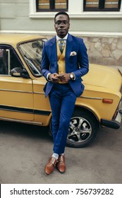 Handsome afro-american fashion model in a blue suit and yellow waistcoat posing on the street.