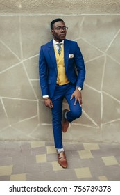 Handsome afro-american fashion model in a blue suit and yellow waistcoat posing near wall.