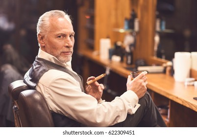 Handsome aged man sitting and enjoying atmosphere in the barbershop