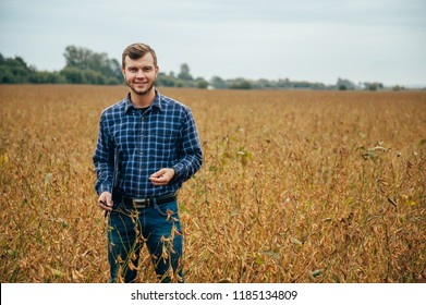 handsome agronomist holds tablet touch pad computer in the soy field and examining crops before harvesting. Agribusiness concept. agricultural engineer standing in a soy field with a tablet.