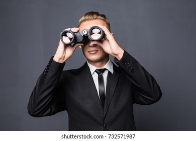Handsome american businessman using binoculars in office on gray background