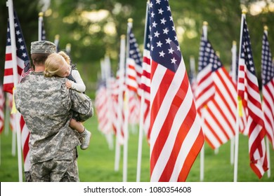 Handsome American Soldier in uniform hugging his 2 year old daughter standing in a field of flags