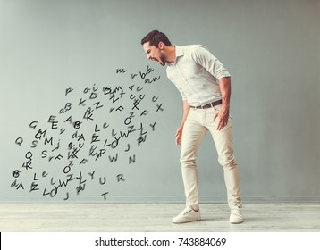Handsome angry man is yelling and the stream of words going out of his mouth, on gray background