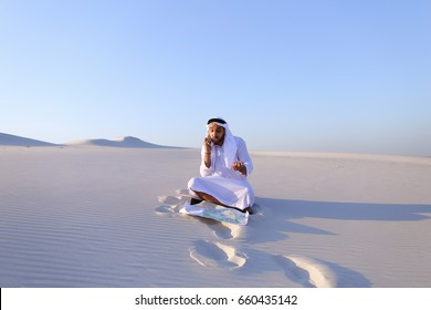 Handsome Arab businessman, talking on cell phone with companion about future construction and general business, looks at drawing and makes adjustments with ballpoint pen, sitting on white clean sand