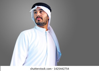 Handsome Arab Man looking away the camera wearing kaffiyeh and traditional kandura menswear in the Middle East Gulf on an isolated gray background