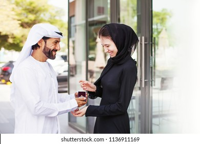 Handsome arab man wearing kandora giving ring as gift to young woman dressed in abaya