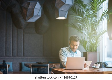 Handsome Arabian guy is making notes from computer