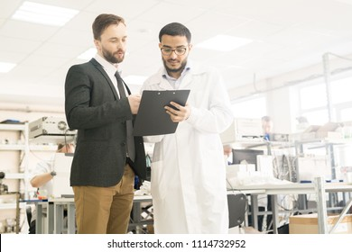 Handsome Arabian technician wearing lab coat and potential investor discussing details of their cooperation while standing at spacious department of pressure transducer factory