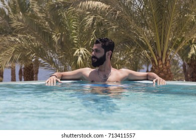 A handsome Arabic Egyptian Attractive man model swimming in a pool at red sea / Sharm Al sheikh  / Egypt in middle east / Africa.