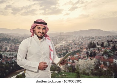 Handsome Arabic guy holding tablet. City view