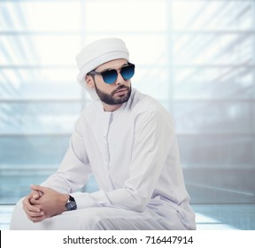 Handsome Arabic man posing with Kandura and sunglasses, Arabic Fashion concept