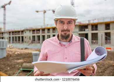 Handsome architect or supervisor standing outdoors on a building site holding a blueprint in his hands looking at the camera with a friendly smile