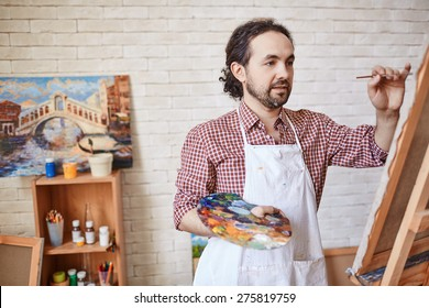 Handsome artist with paintbrush and palette painting on canvas