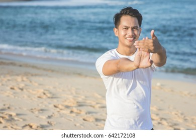 handsome asian athlete warming up before jogging at the beach