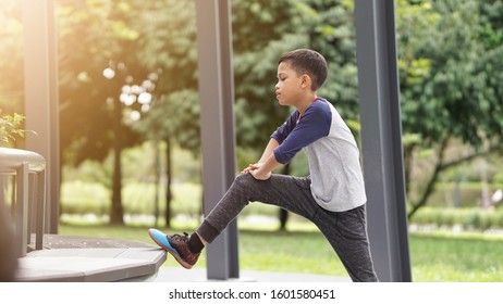 A handsome Asian boy doing his exercise and stretching at the park in the morning.