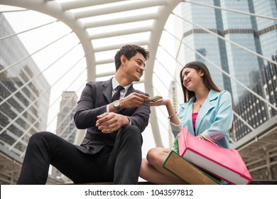 Handsome Asian businessman giving US dollar moneys to beautiful girlfriend or wife to shopping in Bangkok urban city. Happy lifestyle for rich couple.