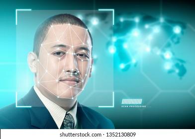 Handsome asian businessman using face recognition over digital world map background. Modern technology concept