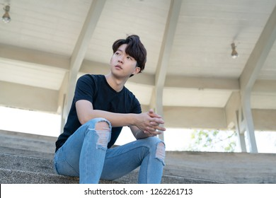 Handsome asian CASUAL man sit on a staircase posing on grandstand background. Portrait of young KOREAN against staircase background.