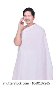 Handsome asian hajj pilgrim with cellphone posing isolated over white background