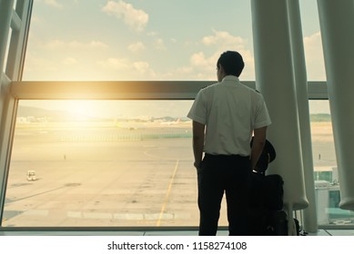 Handsome Asian male pilot is standing in airport terminal and looking outside window. His suitcase is put close to him. Pilot occupation and Aviation concept.