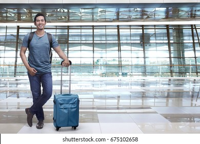 Handsome asian man backpacker holding blue suitcase in the airport terminal