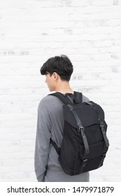 Handsome Asian man with black canvas backpack smiling standing.