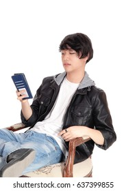 A handsome Asian man in a black leather jacket talking on his cellphone, sitting in a armchair, isolated for white background.