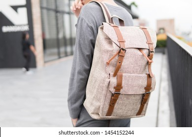 Handsome Asian man with close up white leather backpack smiling standing.