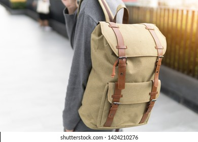 Handsome Asian man with green canvas backpack smiling standing.