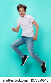 Handsome asian man jumping over blue background.