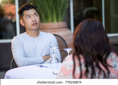 Handsome asian man on an outdoor date with a black female.  The couple are sitting in a restaurant or cafe setup for speed dating.  He looks bored and disappointed.