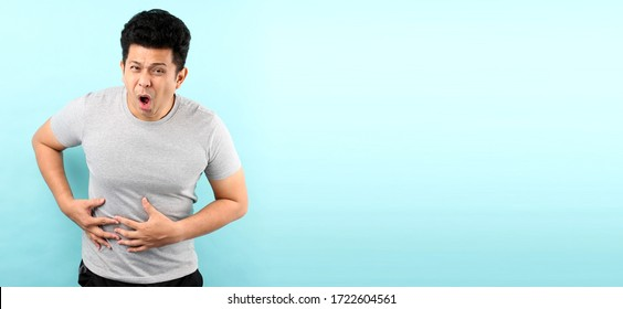 handsome of asian man Sick has stomachache isolated on blue background in studio With copy space.
