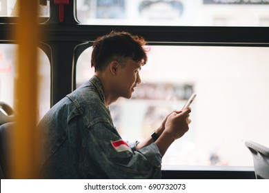 Handsome asian man sitting in city bus and typing a message on the phone.