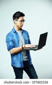 Handsome asian man using laptop on gray background