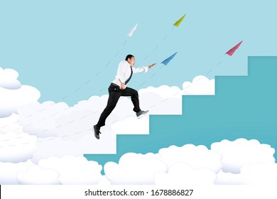 Handsome Asian man wearing a suit while climbing stairs on the clouds, isolated in cyan background with flying paper airplanes